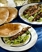 Lamb kebabs on salad and pitta rolls