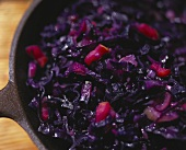 Red cabbage with onions and diced apples in pan