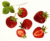 Whole and half strawberries and a strawberry leaf
