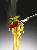 Spaghetti with cheese, tomato slice and basil on fork