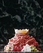 Beef tartar with ingredients on a marble platter