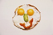 Fried egg face with gherkin nose and pepper mouth