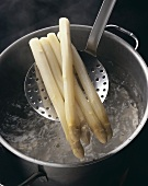White asparagus on a skimmer over boiling water