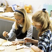 Two girls painting Christmas biscuits