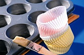 Muffin tin with pastry brush and paper baking cases