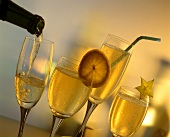 Four glasses of champagne (some decorated with fruit slices)
