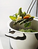 Spring vegetables in cooking pot and on skimmer