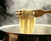 Lifting spaghetti out of a steaming pan with a wooden fork