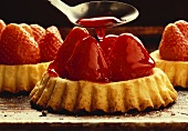 Pouring red glaze over strawberry tartlet