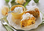 Pieces of coconut cake with dried fruit & bowl of cream