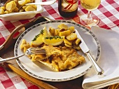 Wiener schnitzel with lemon wedges and fried potatoes