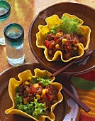 Two taco shells with tomato and bean filling