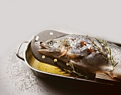 Whole poached salmon in a roasting dish