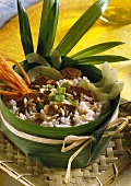 Thai rice dish with pork fillet in banana leaf