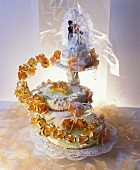 Three-tiered white wedding cake with bride & groom figures