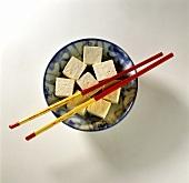 Tofuwürfel auf einem Teller mit Stäbchen