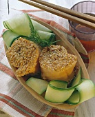 Salmon rolls with sesame coating, with courgettes