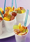 Fruit salad with jelly cubes in plastic pots
