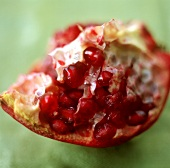 A quarter of a pomegranate on a green background