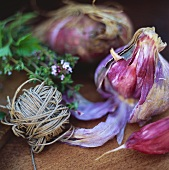 Red garlic and string on wooden board