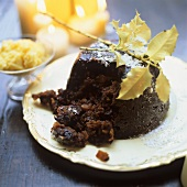 Christmas pudding, cut into; decoration: burning candles