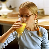 Blond girl drinking orange juice