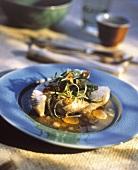 Steamed halibut steak with vegetables in garlic oil