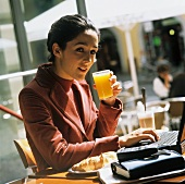 Businesswoman sitting in café with orange juice and laptop