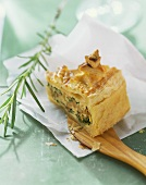 A piece of chanterelle pie with ricotta on baking parchment