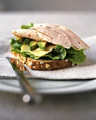Sandwich with turkey breast, avocado, cheese and lettuce