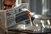 Young woman reading Australian newspaper (café in Sydney)