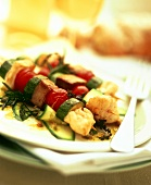 Fish and vegetable kebabs on courgette salad