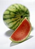 Eine ganze Wassermelone und ein Melonenschnitz