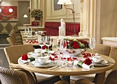 A festively laid table with red roses in a traditional restaurant