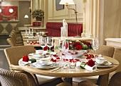 Festlich gedeckter Tisch mit roten Rosen in einem traditionellem Lokal