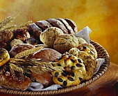 Loaves of bread and rolls with cereal ears in bread basket