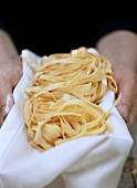 Hands holding home-made ribbon pasta on tea towel