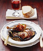 Guinea-fowl with raw ham & aubergines; glass of red wine; bread