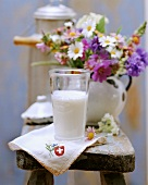 Still life with milk from Switzerland, napkin and flowers