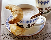 Croissant on a cup of milky coffee