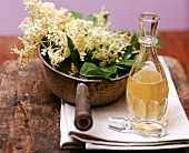 Still life with elderflower syrup and elderflowers