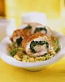 Turkey roulade with spinach filling on vegetables
