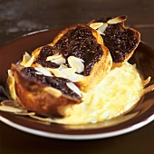 Baked brioches with chocolate sauce and almonds