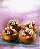 Small strawberry savarins with cream and flaked almonds