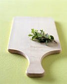 Wooden chopping board and herb sprig