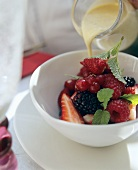 Pouring custard over berry salad