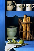 Mediterranean crockery and bread basket in blue cupboard