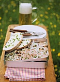 Sausage salad with onions in picnic box; bread & butter; beer