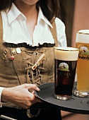 Woman in national dress serving tray of Bavarian beer