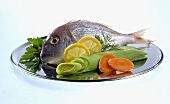 Fresh gilthead bream, garnished with vegetables and lemon